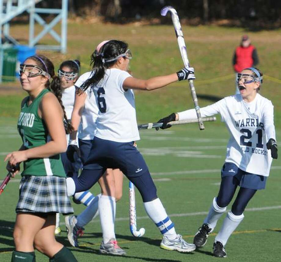Guilford's Jenna Moscarelli, left, walks way from the Wilton celebration after a first-half goal in the Class M state field hockey final won by Wilton. Photo by Peter Hvizdak / New Haven Register Photo: New Haven Register / ©Peter Hvizdak /  New Haven Register