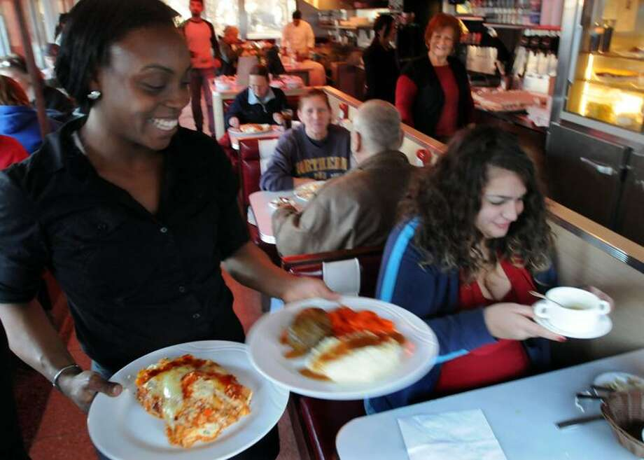 Georgie's Diner in West Haven served free dinners to customers between 3 and 6 p.m. Christmas Eve. Waitress Lena Bell of West Haven serves Jennifer Miskowizcz of Derby and a companion. Photo by Mara Lavitt/New Haven Register
