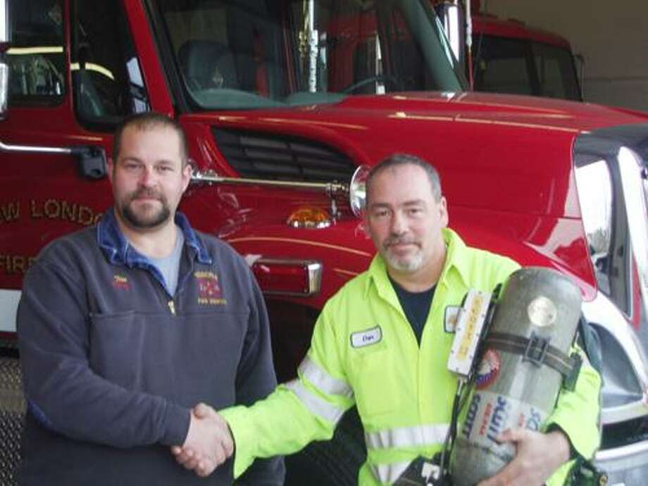 SUBMITTED PHOTO From left is Chief Tim Dodge from the Verona Fire Department and Chief Danny Hartzog from the New London Fire Department. Hartzog is holding one of the newly donated air packs.