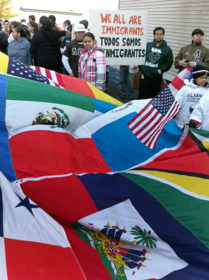 People start to gather for the East Haven Unity March Saturday. The flags of many nations combine to form one big one. Arnold Gold/Register