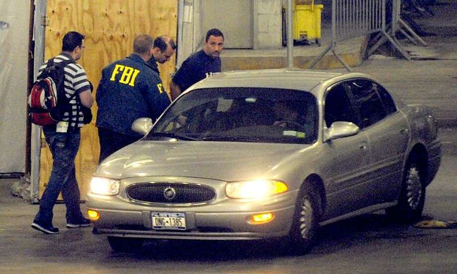 Richard Palase, standing right, a New York City Police Department detective, was one of 15 people, including two firefighters, who were arrested in connection with a New York City gambling ring. Palase is seen being transferred by FBI agents in the garage of the Jacob K. Javits Federal Building. Associated Press Photo: AP / FR151332 AP