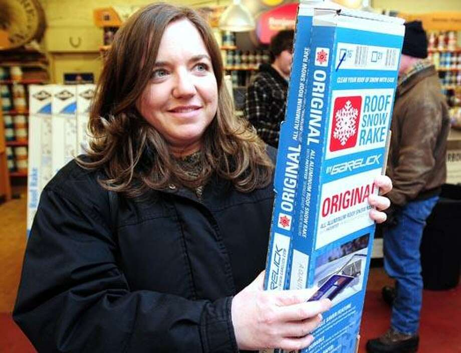 Tara Gado of Wallingford purchases a roof rake at R.W. Hine Hardware in Cheshire on 2/1/2011. (Photo by Arnold Gold/New Haven Register)