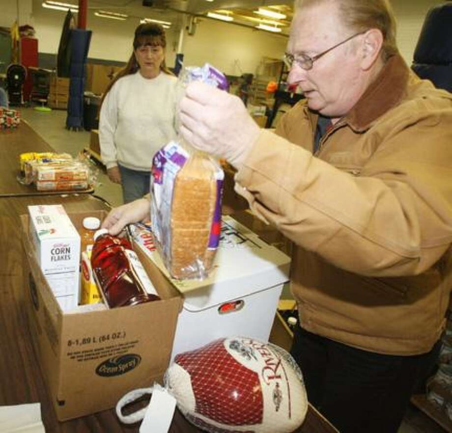 Dispatch Staff Photo by JOHN HAEGER (Twitter.com/OneidaPhoto) Sandra and Eric Lawrence pack up food baskets to be given to families on Thursday, Dec. 22, 2011 at the Salvation Army in Oneida.