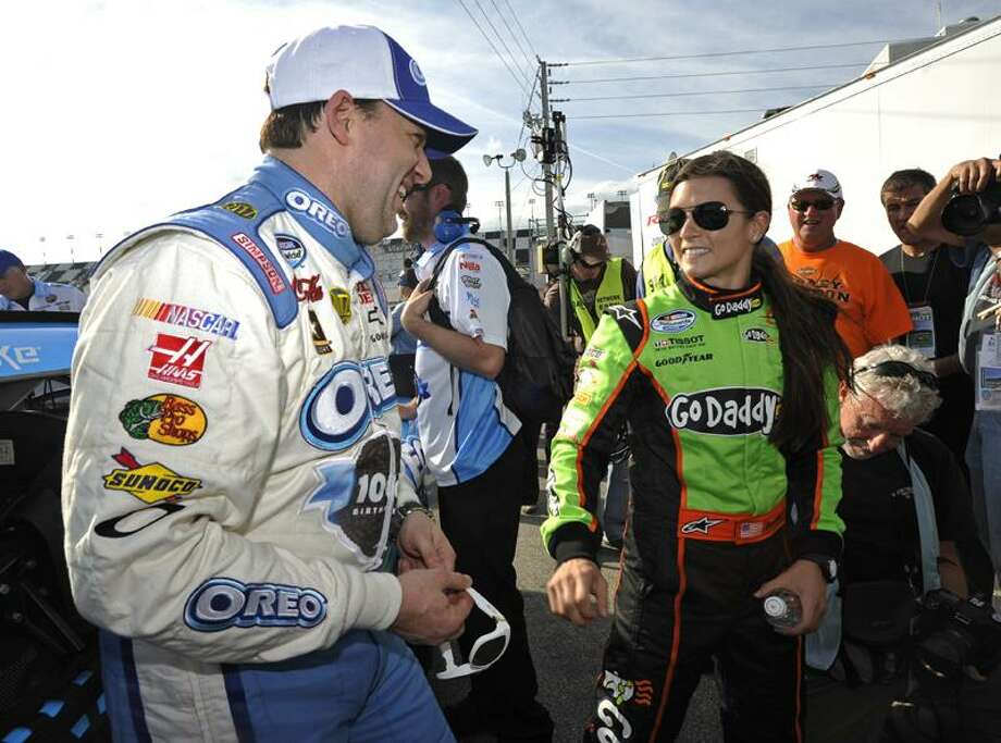 Danica Patrick, right, talks with Tony Stewart, left, after qualifying for Saturday's NASCAR Drive4COPD 300 auto race in Daytona Beach, Fla., Friday, Feb. 24, 2012. Patrick won the pole position for the race. (AP Photo/Rainier Ehrhardt) Photo: AP / FR155171 AP