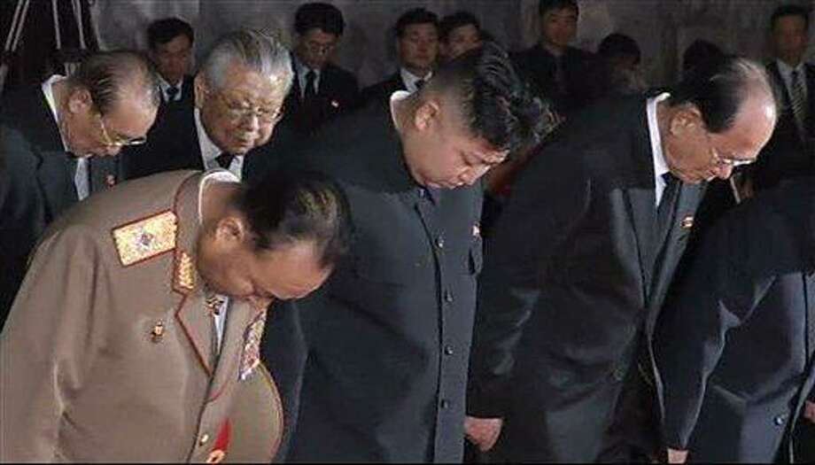 "In this image made from AP video, Kim Jong Un, centre, North Korean leader Kim Jong Il's youngest known son and successor, bows as he visits the body of the senior Kim with top military and Workers' Party officials in a memorial palace in Pyongyang, North Korea, Tuesday, Dec. 20, 2011. Indicating the leadership transition in the world's only communist dynasty is on track, Kim Jong Un  visited the body with top military and Workers' Party officials and held what state media called a ""solemn ceremony"" in the capital, Pyongyang, as the country mourned. (AP Photo) TV OUT Photo: AP / AP"