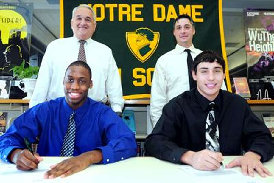 David Rose, Jr., (seated left) and Sean Goldrich (seated right) are photographed with their signed letters of intent with their coach, Tom Marcucci back left), and assistant coach, Joe DeCaprio (back right), at Notre Dame of West Haven on 2/3/2011.Photo by Arnold Gold/New Haven Register     AG0402A