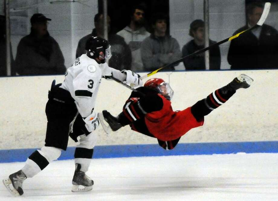 Ryan Moore of Guilford, left, checks Spencer Hacket of Cheshire during first-period hockey action Thursday at DiLungo Rink in East Haven. Guilford beat Cheshire 3-2. Photo by Peter Hvizdak / New Haven Register