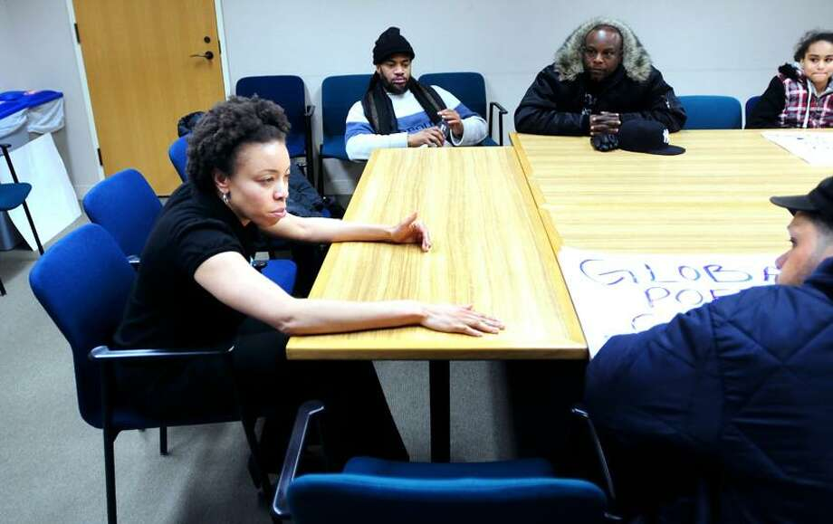 Community Services Administrator Chisara Asomugha (left) speaks with Ismael Correa (far right) and others concerning homeless issues at City Hall in New Haven on 2/24/2012.Photo by Arnold Gold/New Haven Register   AG0440E