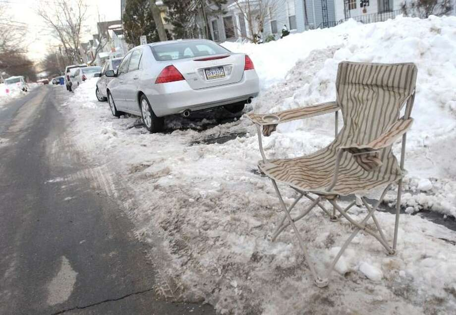 Brad Horrigan/Register  Some residents of Bishop Street in New Haven have placed items such as chairs in cleared parking spaces to save the spot.