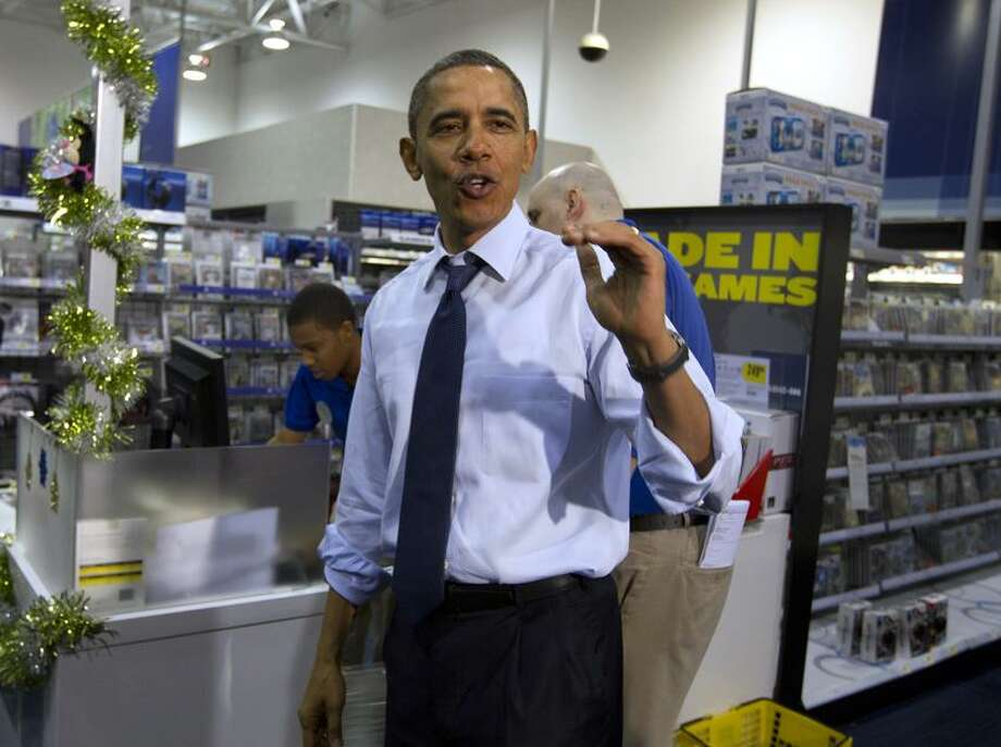 President Barack Obama does his part for the economy, shopping for Christmas gifts for his family at a Best Buy Wednesday in Alexandria, Va. Photo: AP / AP2011