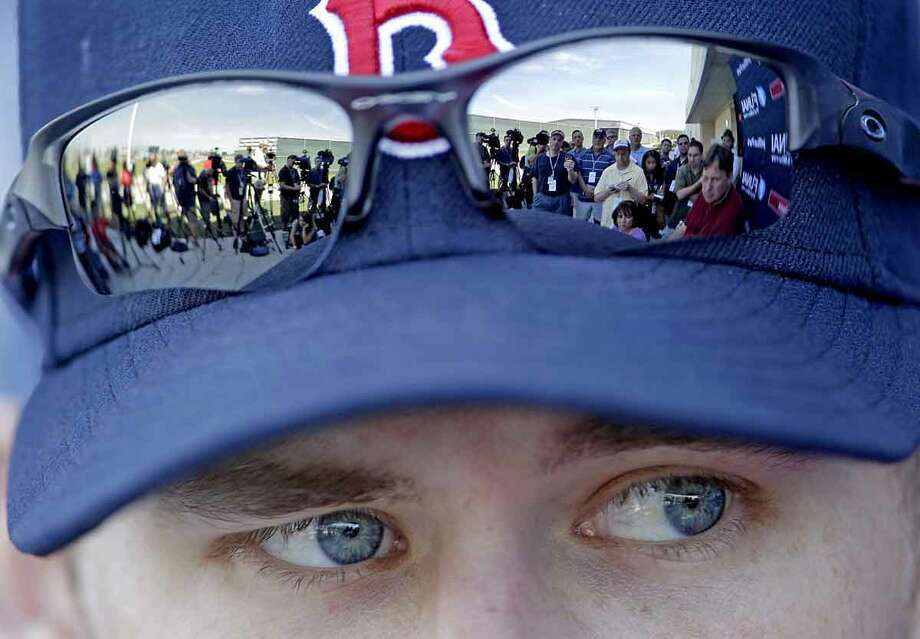 Members of the media are reflected in the sunglasses of Boston Red Sox pitcher Daniel Bard as he speaks during a news conference following a baseball spring training workout Tuesday in Fort Myers, Fla. Associated Press Photo: ASSOCIATED PRESS / AP2012