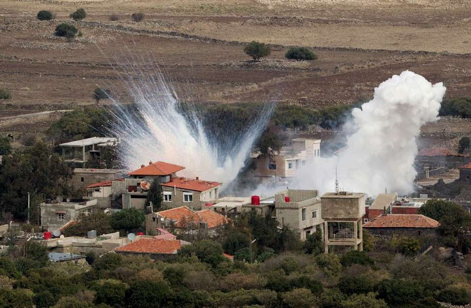 "Smoke rises after shells fired by the Syrian army explode in the Syrian village of Bariqa, Monday, Nov. 12, 2012. The Israeli military says ""Syrian mobile artillery"" was hit after responding to stray mortar fire from its northern neighbor. The incident marked the second straight day that Israel has responded to fire from Syria that does not appear to be aimed at Israeli targets, nonetheless Israel has promised a tough response if the fire continues. (AP Photo/Ariel Schalit) Photo: ASSOCIATED PRESS / AP2000"