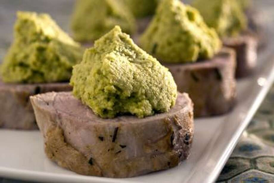 This Jan. 10. 2011 photo shows pork tenderloin with roasted fava beans and garlic in Concord, N.H.  This recipe works with either pork tenderloin or chicken, though you will need to adjust the cooking time for the chicken.       (AP Photo/Larry Crowe) Photo: AP / FR41490 AP