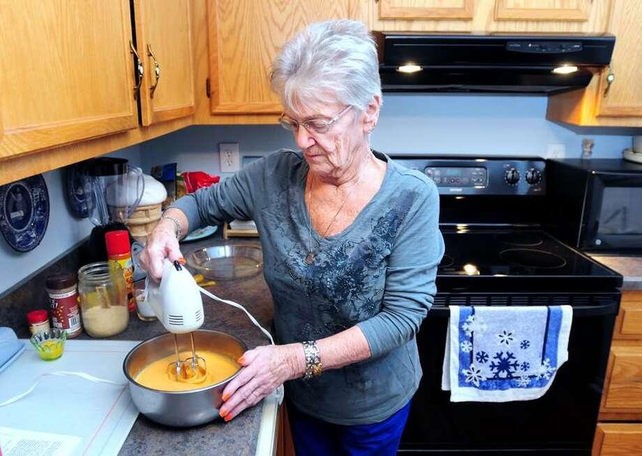 Arnold Gold/Register photo: Fran Bartlett mixes up ingredients for her Crustless Pumpkin Pie in her North Haven kitchen recently.