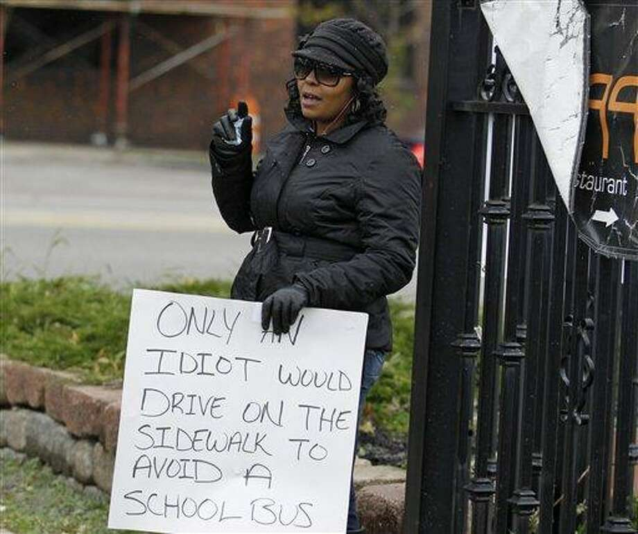 Shena Hardin holds up a sign to serve a highly public sentence Tuesday, Nov. 13, 2012, in Cleveland, for driving on a sidewalk to avoid a Cleveland school bus that was unloading children. A Cleveland Municipal Court judge ordered 32-year-old Hardin to serve the highly public sentence for one hour Tuesday and Wednesday. (AP Photo/Tony Dejak) Photo: AP / AP