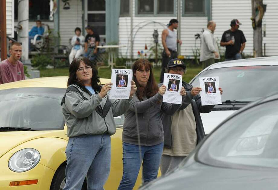 Family friends hold up missing posters for Celina Cass for passing cars to view outside the family residence, at rear, in Stewartstown, N.H., Wednesday, July 28, 2011. Cass, 11, has been reported missing since she was last seen at her home on Monday.(AP Photo/Charles Krupa) Photo: AP / AP2011