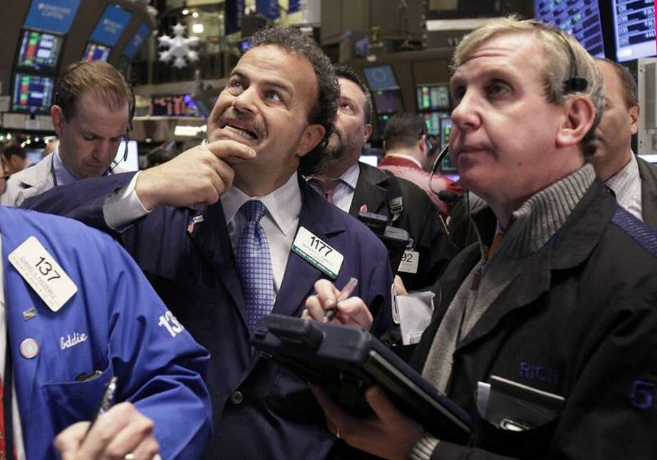 Traders Gerard Farco, left, and Richard Cohen work on the floor of the New York Stock Exchange Tuesday. Stocks surged after the opening bell following encouraging signs out of Europe and a jump in apartment buildings in the U.S. (Associated Press) Photo: AP / AP