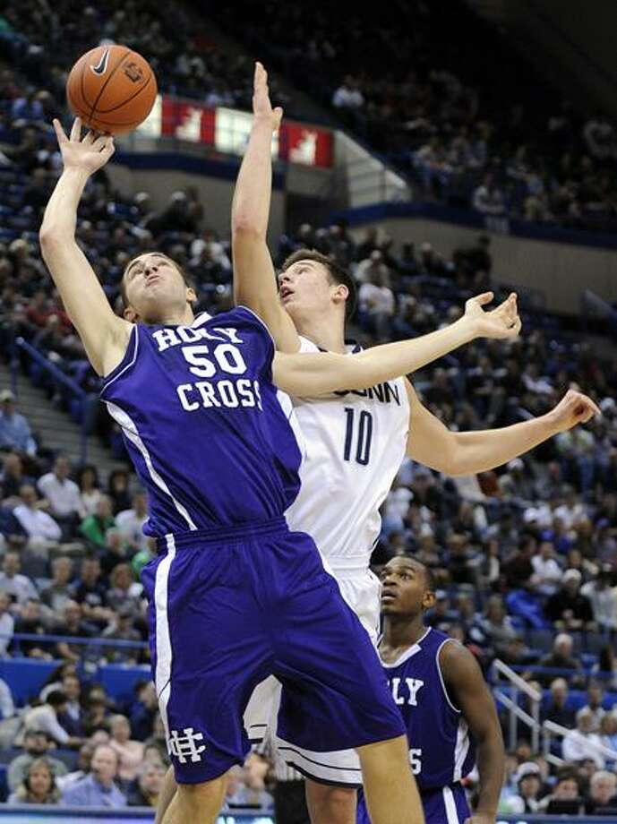 UConn's Tyler Olander (10), shown here battling for a rebound against Holy Cross, will be competing against his brother Ryan and his Fairfield teammates in Thursday's game at the XL Center (AP photo). Photo: AP / AP2011