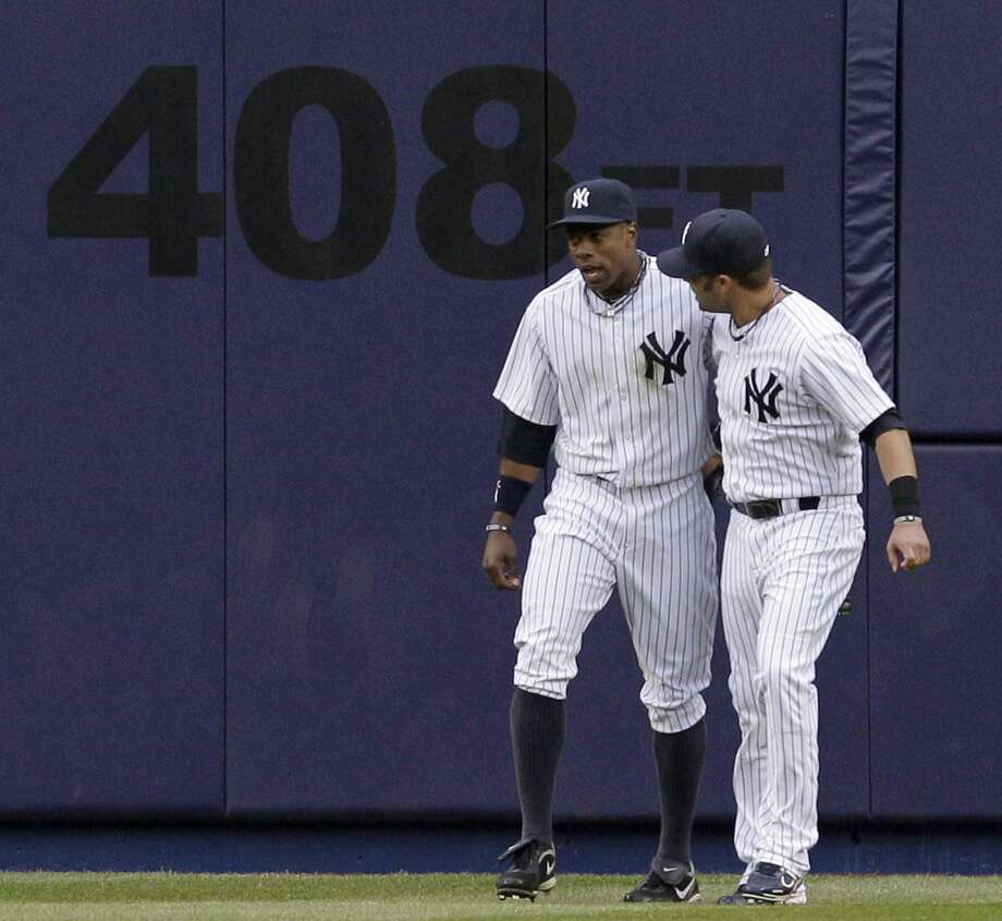 New York Yankees right fielder Nick Swisher, right, congratulates Curtis Granderson who caught Brandon Inge's ninth-inning flyout near the center field wall in the Yankees 6-3 opening day win  over the Detroit Tigers at Yankee Stadium on Thursday, March 31, 2011 in New York. (AP Photo/Kathy Willens) Photo: AP / AP