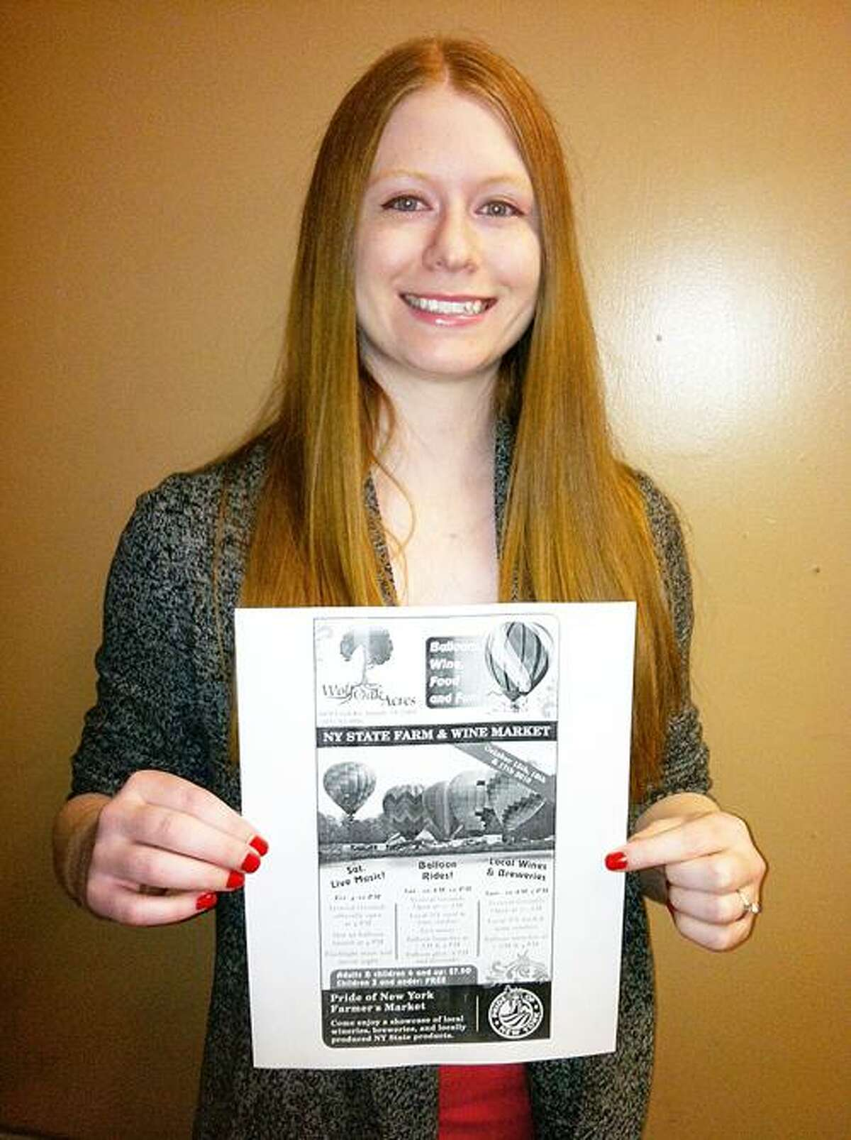 """Dispatch Staff Photo by CAITLIN TRAYNOR Jen Curtis holds a printout of """"Balloons, Wine, Food and Fun,"""" a black and white ad that won first place in the Best Single Black & White ROP Ad"""" category for the Suburban Newspapers of America Advertising & Promotions Contest."""