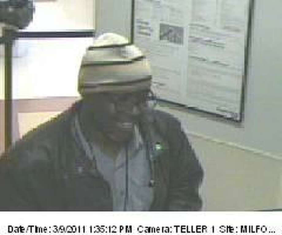 The man seen in this bank video surveillance photo provided by Milford police has been charged with a March 9 robbery in Milford. The suspect, Michael Carlton Reddick, 56, of Hamden, also is charged with a March 16 bank robbery in Hamden.
