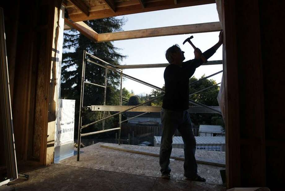 Will Capper works on a new house in Palo Alto, Calif., Nov. 22. Rising interest from would-be buyers is leaving U.S. homebuilders less pessimistic about the housing market. But tighter lending standards are still keeping many potential buyers from purchasing new homes.(Associated Press) Photo: AP / AP