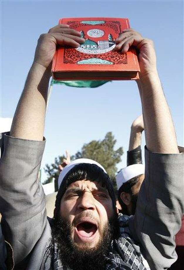 An Afghan protester holds a copy of Islam's holy book Quran as he shouts slogans during an anti-US demonstration in Jalalabad, east of Kabul, Afghanistan, Wednesday. Associated Press Photo: AP / AP