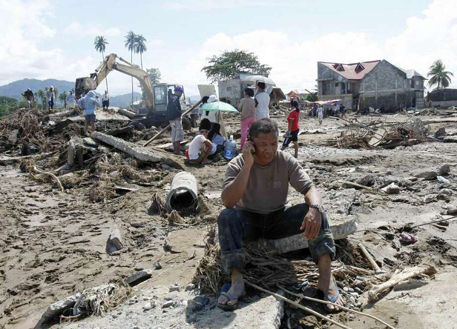Cristio Tingson talks on his cell phone as workers use a backhoe to search for victims of his buried house Sunday. Associated Press Photo: AP / AP2011