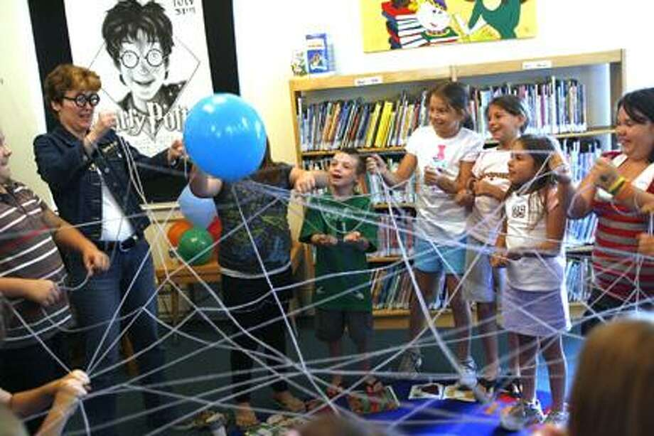 Dispatch Staff Photo by JOHN HAEGER (twitter.com/oneidaphoto)Children bounce a balloon off of a web they made by passsing yarn back and forth during a birthday party for Harry Potter at the Canastota Public Library on Thursday, July 28, 2011.