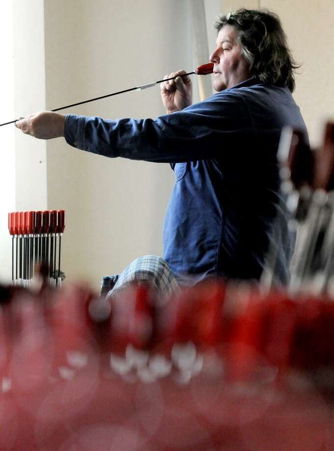 Monte Marquis, an employee of Dewey Manufacturing, examines a rifle cleaning rod. (Peter Hvizdak/Register)
