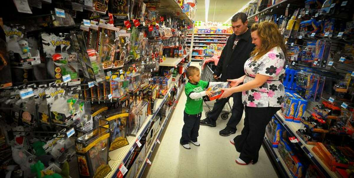 Kevin and Jolie Lewis shop with their son, Alex, for a family they adopted for Christmas at a Kmart in Omaha, Neb. The Lewises had their layaway paid off at Kmart by an unknown good Samaritan. (Associated Press)