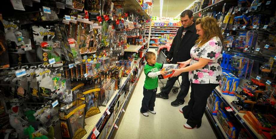 Kevin and Jolie Lewis shop with their son, Alex, for a family they adopted for Christmas at a Kmart in Omaha, Neb. The Lewises had their layaway paid off at Kmart by an unknown good Samaritan. (Associated Press) Photo: AP / AP2011