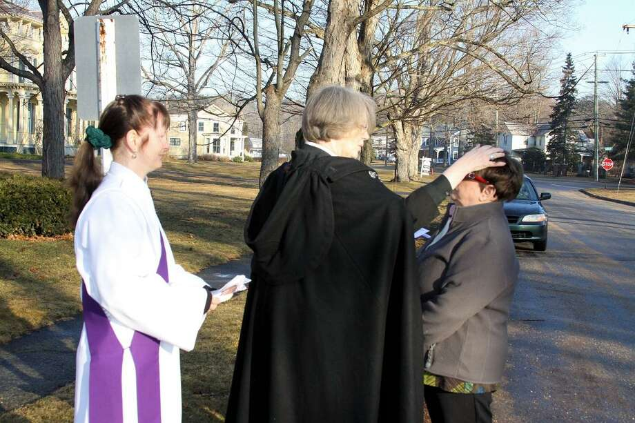 The Rev. Salin Low, rector, and the Rev. Denise Adessa, deacon (with purple stole), offer Ashes to Go at St. John's Episcopal Church in New Hartford. Photo by Kathryn Boughton/Litchfield County Times