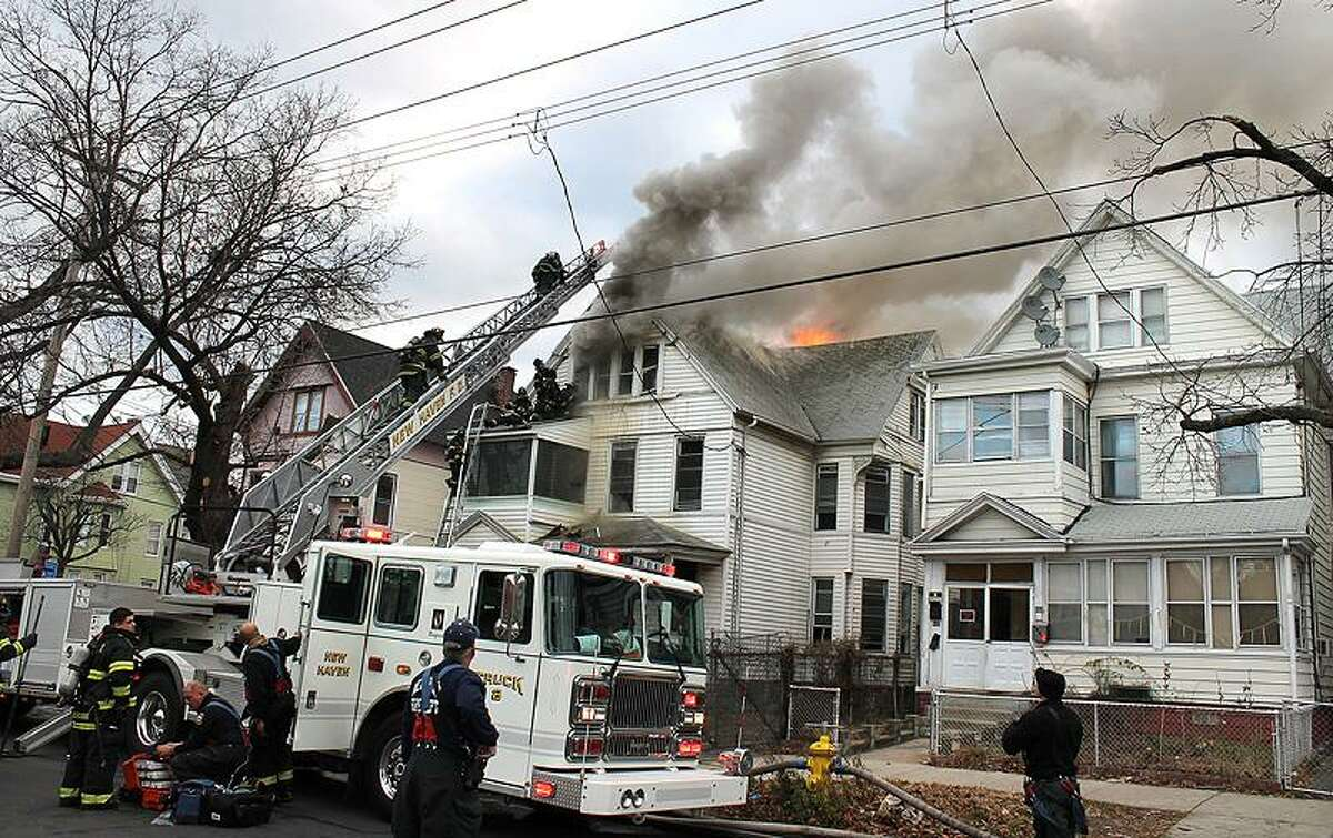 New Haven firefighters battle a two-alarm blaze at a vacant house at 439 Howard Avenue. Photo by Joe Ciscone/Special to the Register.