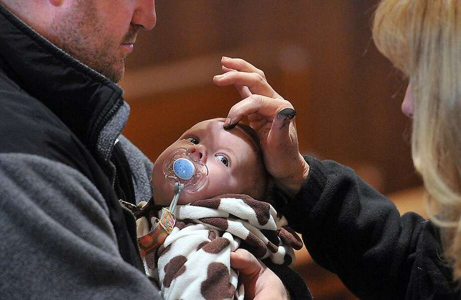 3-Month-old Mara Picciano has ashes applied by Eucharistic Minister, Charlene Armellino during Ash Wednesday services at St. Bernadette's Church in New Haven. Holding Picciano is her father, Nick. They are from New Haven. Photo- Peter Casolino/New Haven Register 02/22/12
