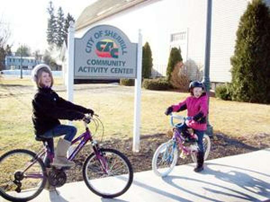 Photo Special for the Dispatch by MIKE JAQUAYS Jenna Watson, 10, left, and sister Emily Watson, 7, of Sherrill pose on their bikes in front of the Sherrill Community Activity Center on East Hamilton Avenue. The CAC will host the City of Sherrill Bike Auction on April 16, kicking off with a general preview at 9:30 a.m.