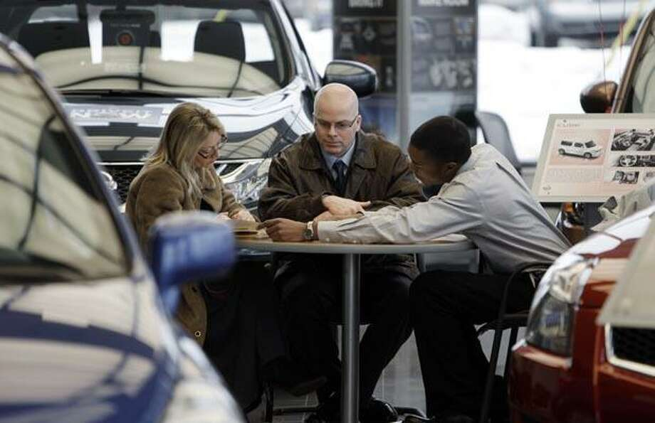 In this March 14, 2011 photo, Kelley and Ed Postal, of Pinckney, Mich., from left, work with salesman Darnell Forte at a Nissan dealership in Ann Arbor, Mich. Consumer spending rises at fastest pace since October, led by purchases of autos and gasoline.(AP Photo/Paul Sancya) Photo: AP / AP