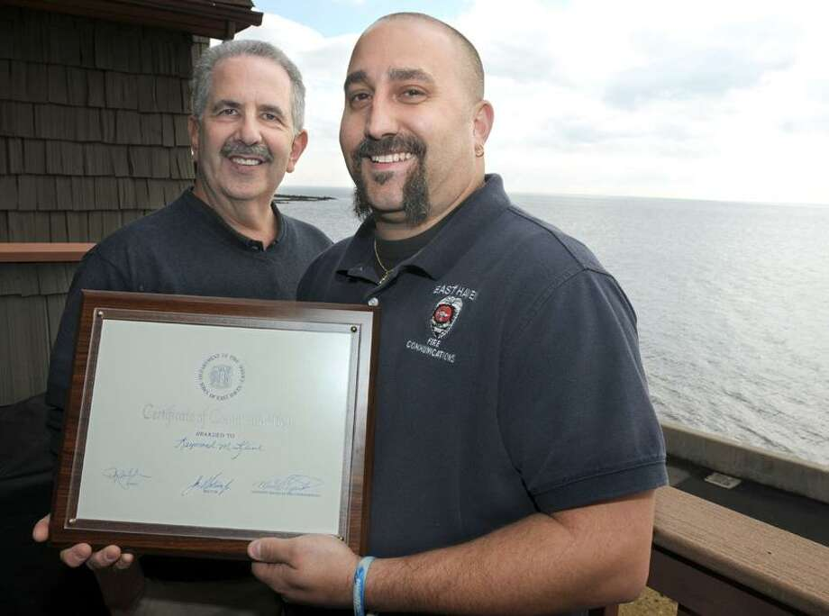 Eric Stolzman, left, stands at home in East Haven with East Haven Fire Department dispatcher Raymond Kline. When Stolzman was worried about his two sons boating in Maine, Kline aided in their rescue. Kline was commended for his response to Stolzman's call. Mara Lavitt/Register