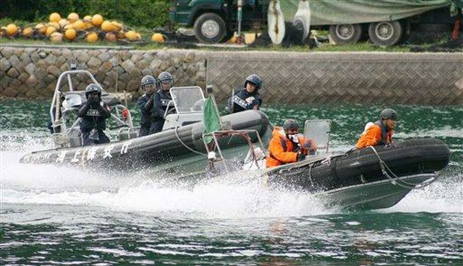 """Japanese coast guard officials on boat patrol in a bay during their security drill in Taiji, a Japanese fishing village under fire for dolphin hunts, central Japan Wednesday, July 27, 2011. Wakayama prefectural police says the drill Wednesday was aimed at guarding the Taiji town and its residents from violent protests by atavists ahead of a hunting season starting September. About 100 police and coast guard officers gathered in the bay - the scene of an Oscar-winning film """"The Cove"""".  (AP Photo/Kumano Shimbun via Kyodo News) Photo: AP / Kyodo News"""