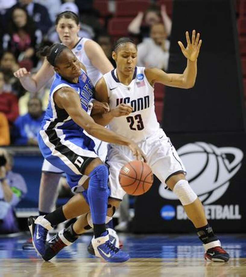 Duke's Karima Christmas, left, battles for control of the ball against Connecticut's Maya Moore (13) in the first half of an NCAA women's college basketball tournament regional final, Tuesday, March 29, 2011, in Philadelphia. (AP Photo/Barbara Johnston) Photo: AP / Barbara Johnston