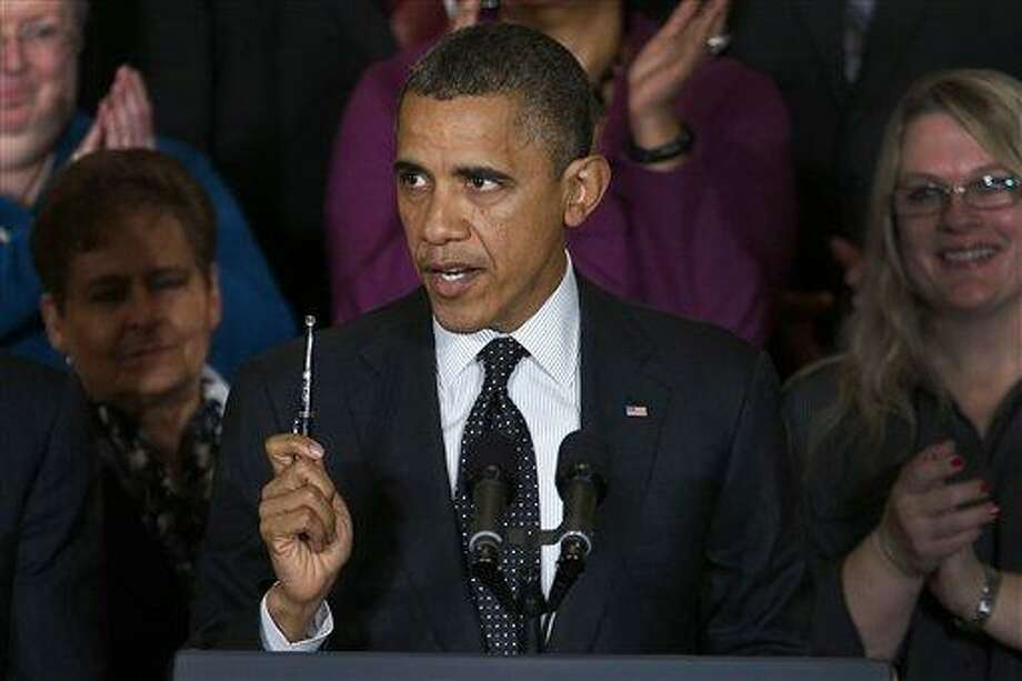President Barack Obama holds up a pen as he speaks about the economy and the deficit, Friday, Nov. 9, 2012, in the East Room of the White House in Washington. (AP Photo/Carolyn Kaster) Photo: AP / AP