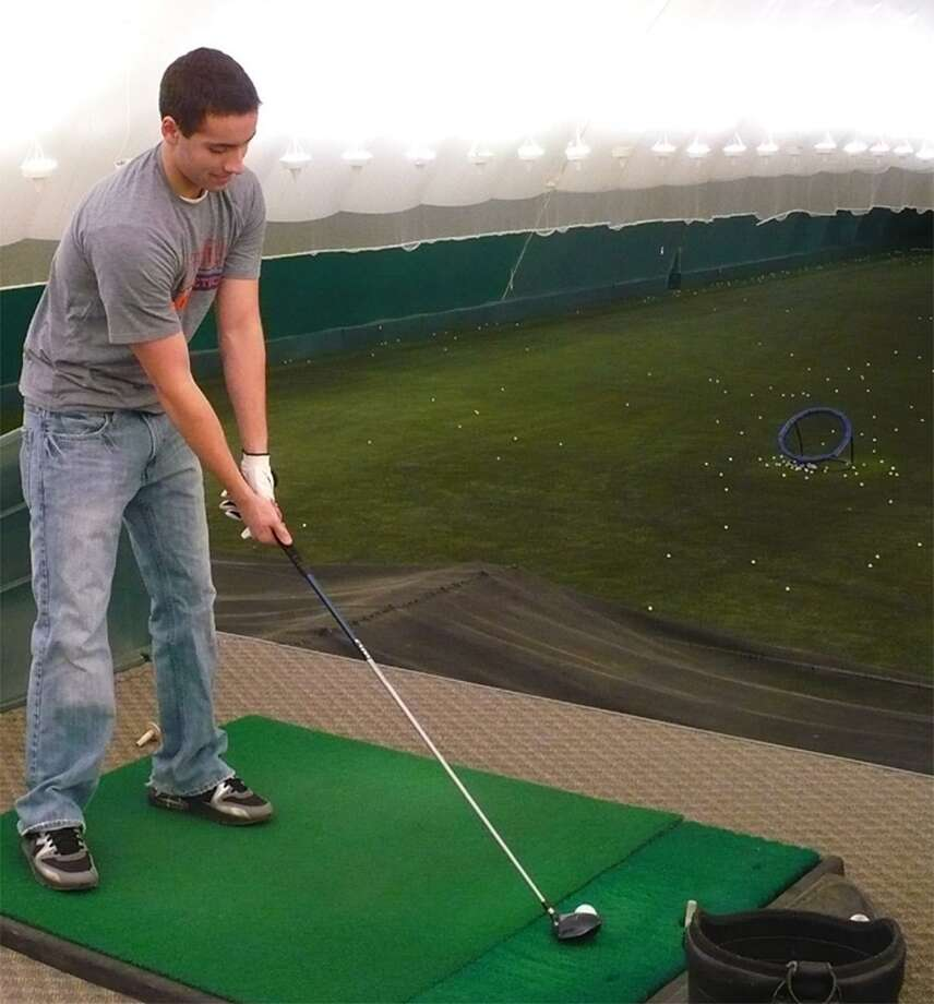 Dispatch Staff Photo by DAVID M. JOHNSON Oneida golfer Ryan Harrigan hits practice balls from the safety of the Golf Dome at Turning Stone Casino and Resort in Verona Monday.