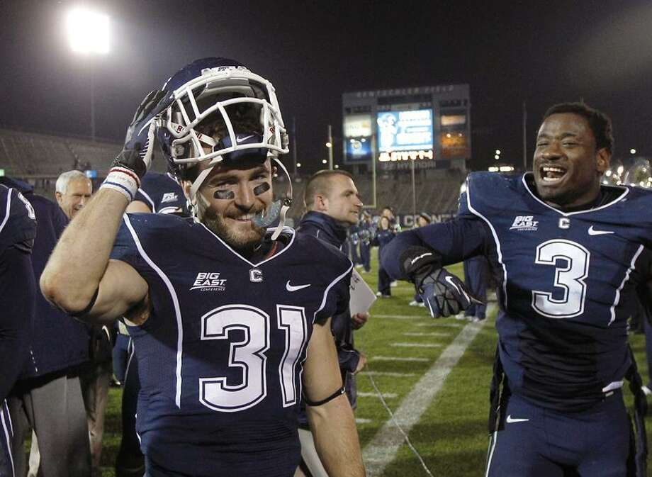 Connecticut wide receiver Nick Williams (31) smiles as he celebrates with teammate linebacker Sio Moore (3) after the team's 24-17 win in an NCAA college football game against Pittsburgh in East Hartford, Conn., Friday, Nov. 9, 2012. Williams returned a punt 80 yards for a touchdown. (AP Photo/Charles Krupa) Photo: AP / AP2012