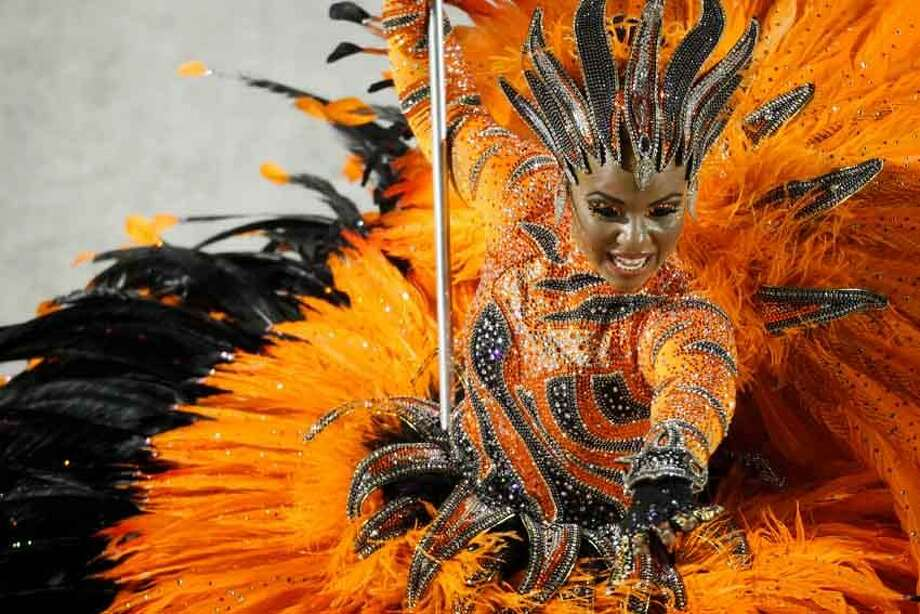 A dancer of Porto da Pedra samba school parades during carnival celebrations at the Sambadrome in Rio de Janeiro, Brazil, Monday. Millions watched the sequin-clad samba dancers at Rio de Janeiro's iconic Carnival parade. Associated Press Photo: ASSOCIATED PRESS / AP2012
