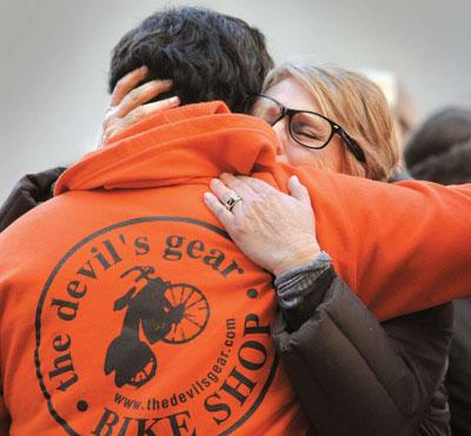 Randi Dubey, Mitchell Dubey's mother, hugs an employee of Devil's Gear Bicycle Shop as she arrives for her son's memorial service. (Melanie Stengel/Register)