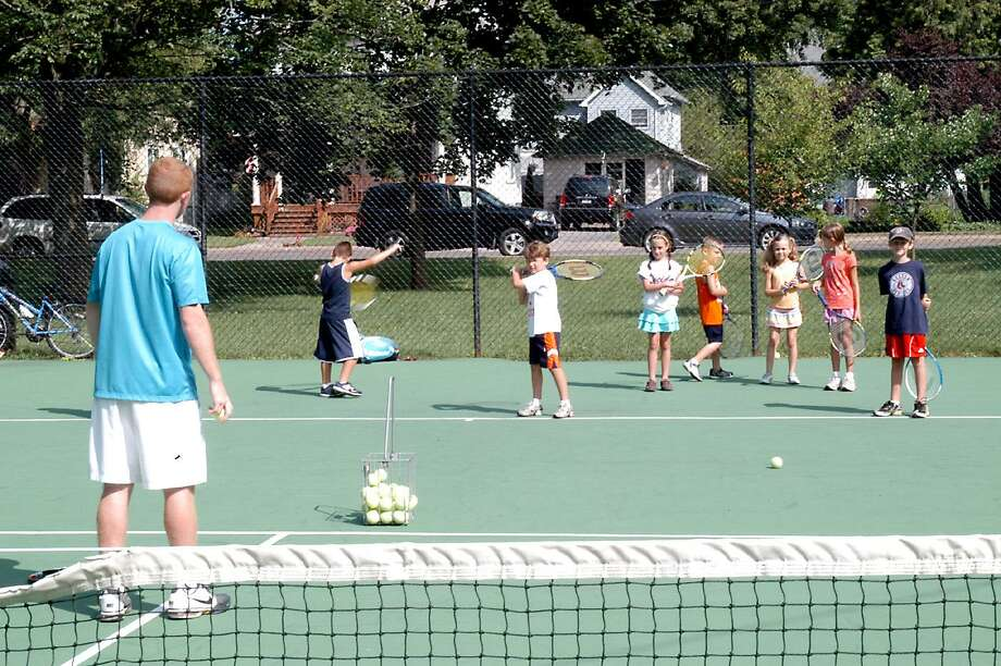 Dispatch Staff Photo by DAVID M. JOHNSONOneida alum Trevor Haskell, left, instructs kids how to prepare to hit a forehand at Allen Park on Tuesday, July 26, 2011.