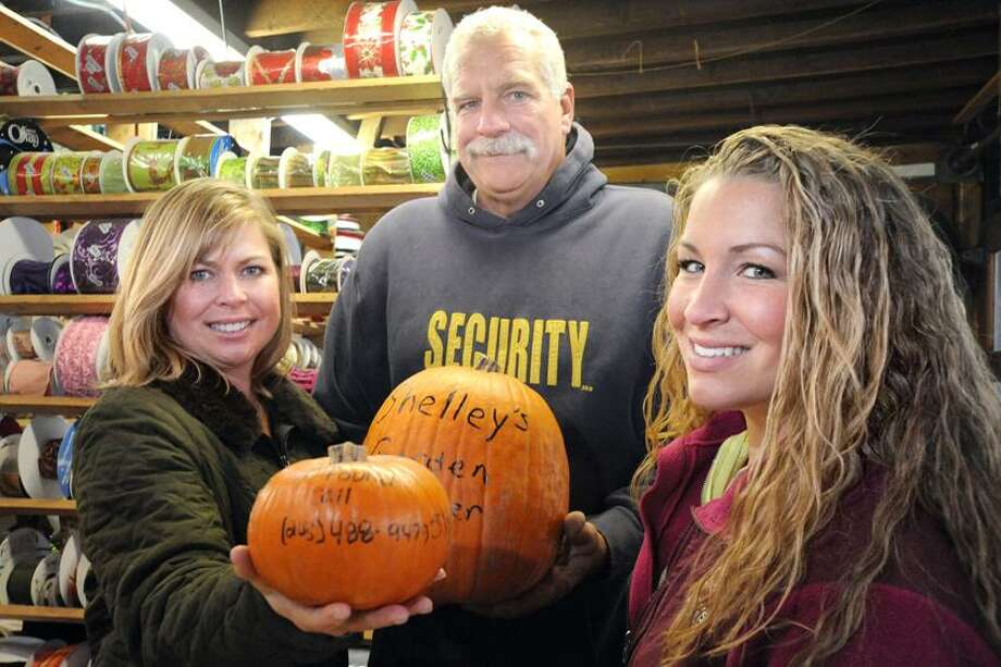 Christiane, John and Taylor Chambers show a couple of the pumpkins they released into Long Island Sound prior to Hurricane Sandy at Shelley's garden Center on Main Street in Branford. vm Williams/Register