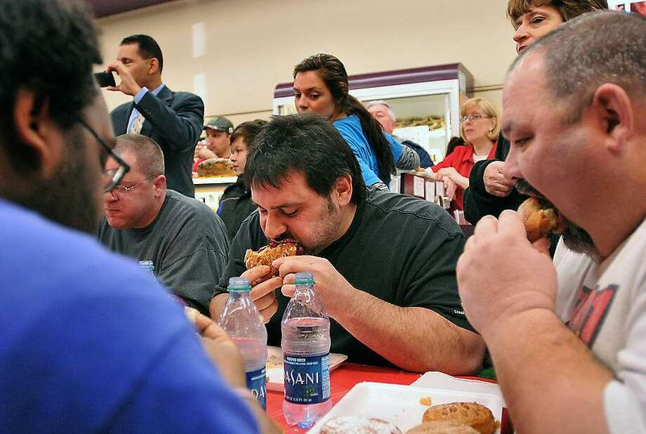 """Gentleman"" Joe Menchetti of Cheshire, center, on his way to another win during the 15th annual  Paczki-eating contest at Eddy's Bake Shop in Ansonia. Menchetti ate 12 Paczki's in five minutes. Photo- Peter Casolino/New Haven Register 02/21/12"
