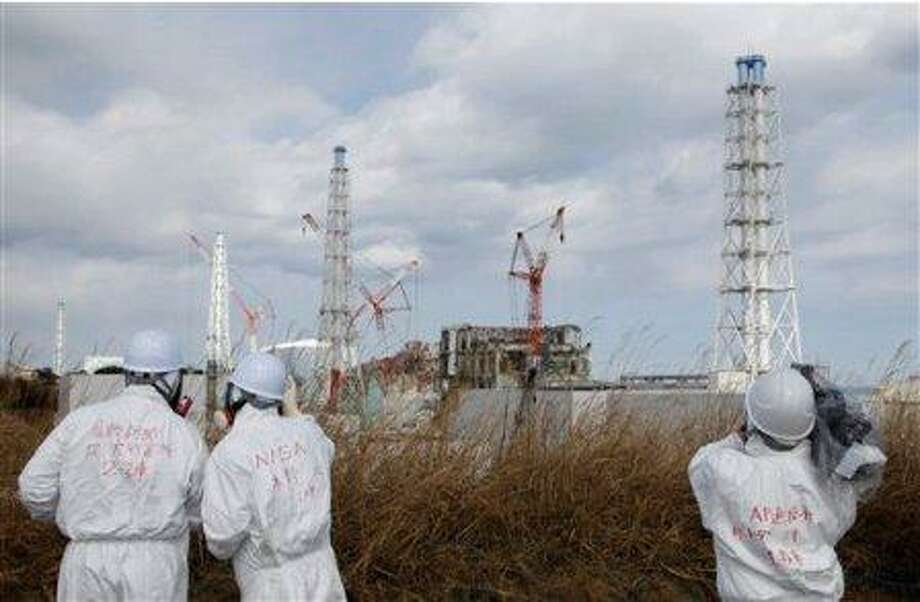 Members of the media wearing protective suits and masks report, escorted by an official of Nuclear and Industrial Safety Agency, second left, at Tokyo Electric Power Co.'s tsunami-crippled Fukushima Dai-ichi nuclear power plant in Fukushima prefecture, northeastern Japan, Monday, Feb. 20, 2012. Japan next month marks one year since the March 11 tsunami and earthquake, which triggered the worst nuclear accident since Chernobyl in 1986. (AP Photo/Issei Kato, Pool)