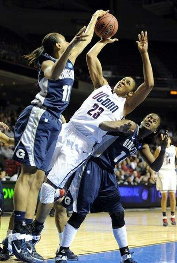 Connecticut's Maya Moore (23) battles for the rebound against Georgetown's Andrea White, left, and Sugar Rodgers (14) in the first half of an NCAA women's college basketball tournament regional semifinal, Sunday, March 27, 2011, in Philadelphia. (AP Photo/Barbara Johnston) Photo: AP / Barbara Johnston